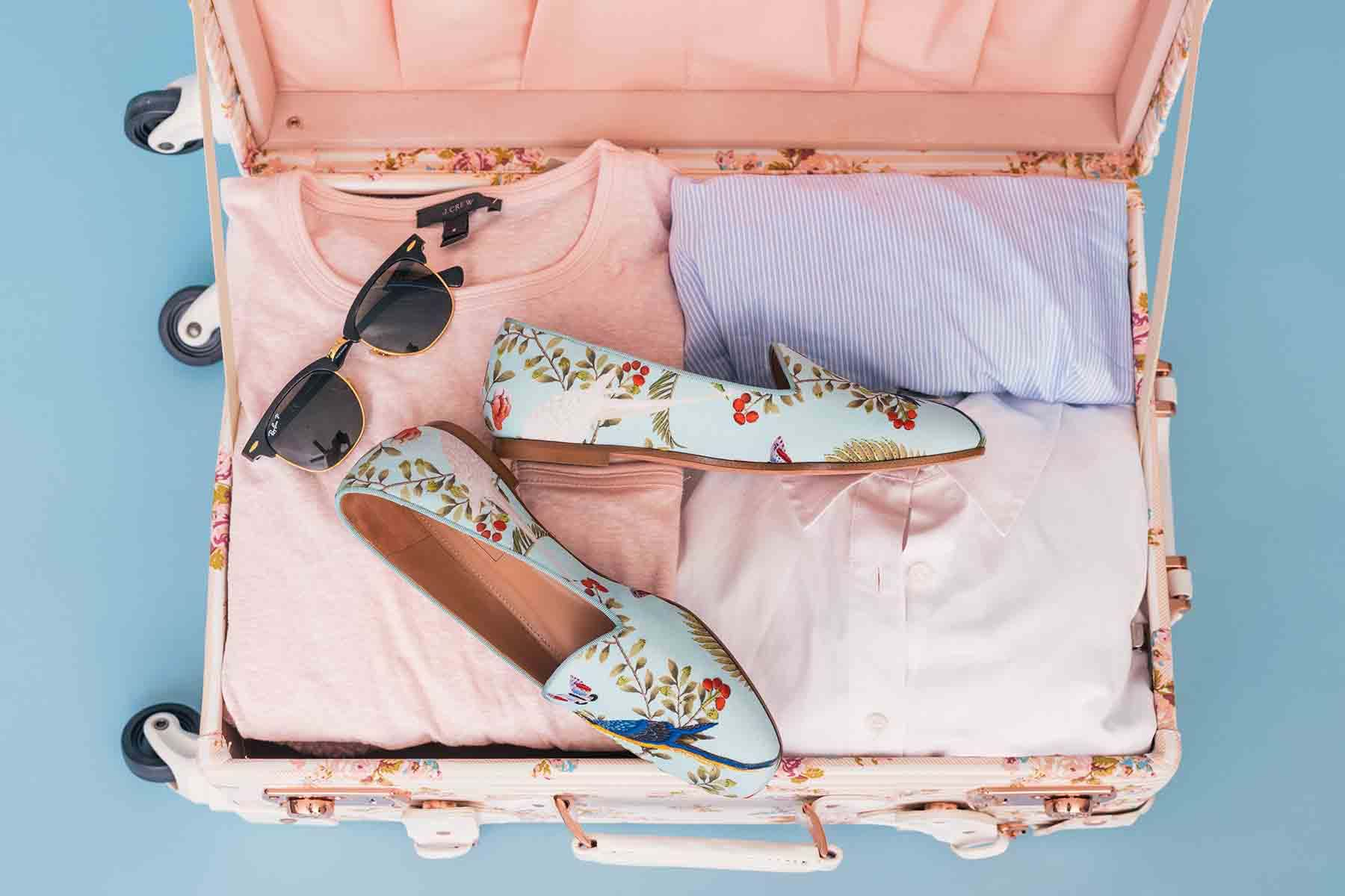 A pink suitcase filled with clothing, shoes, and sunglasses