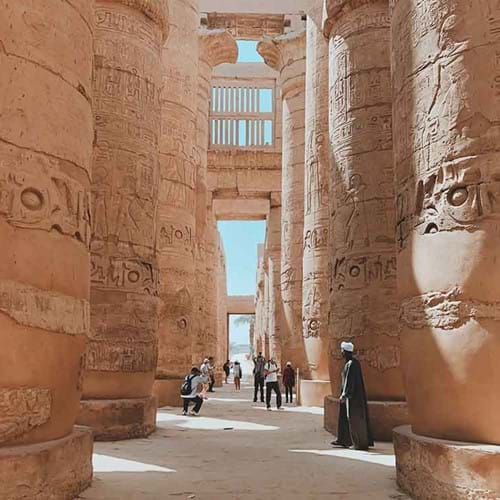 Photo of people touring large, carved brown pillars in Karnak, Egypt