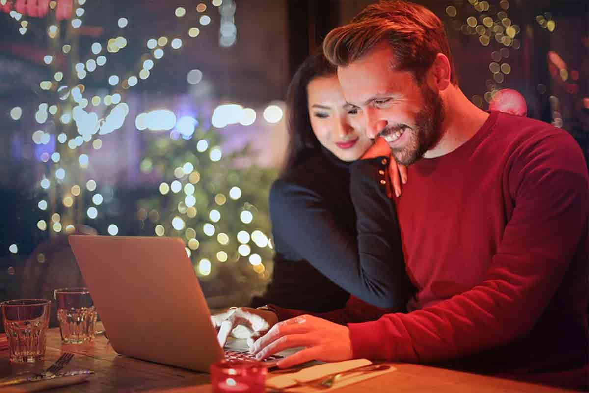 Photo of smiling couple sitting in restaurant using their laptop