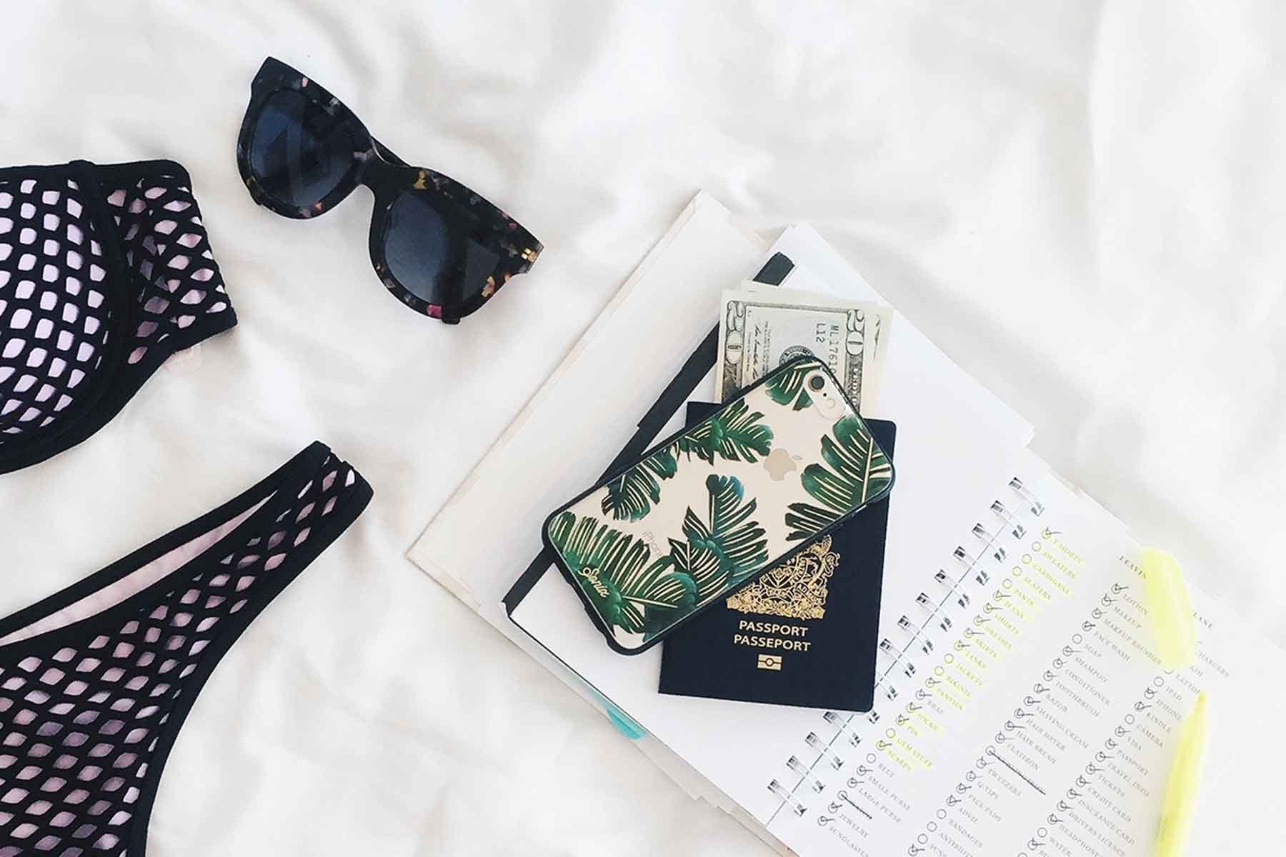 Photo of swimsuit, sunglasses, passport, cash, phone and planner