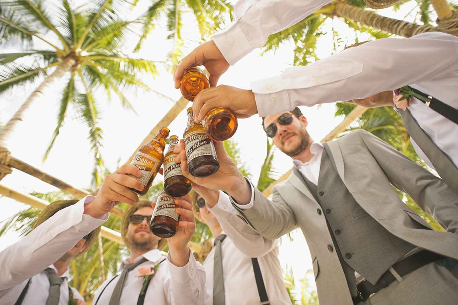 Photo of men in suits toasting beer bottles near palm trees
