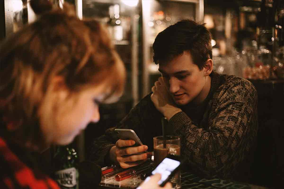 Photo of young people sitting at table with drinks, looking at their phones