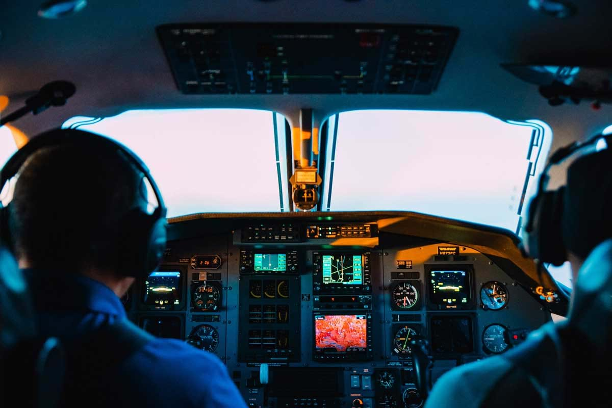 Two pilots sitting in an airplane cockpit with a lit dashboard