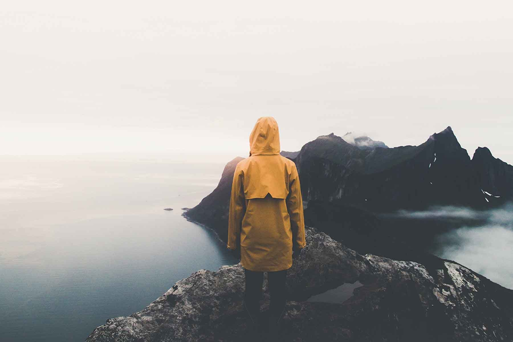Photo of person  in yellow raincoat standing on cliff by ocean