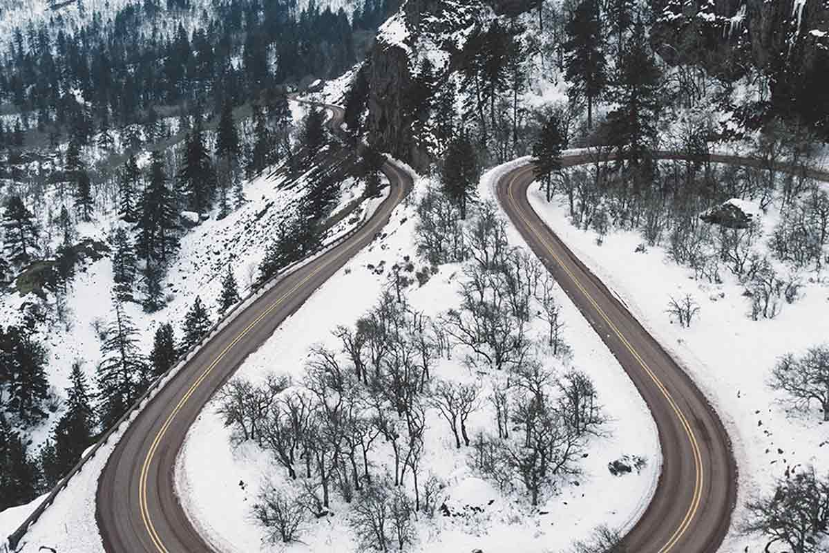 Aerial view of curvy road in snowy mountains
