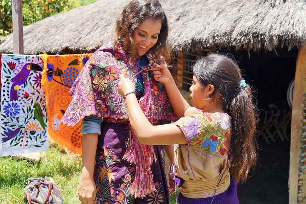 Photo of girl putting colorful shawl on woman in Zincantan, Chiapas, Mexico