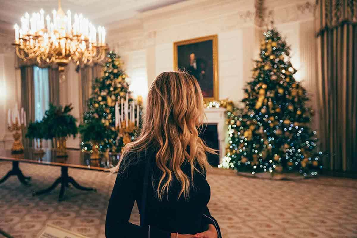 Woman looking away in festive, holiday-decorated ballroom