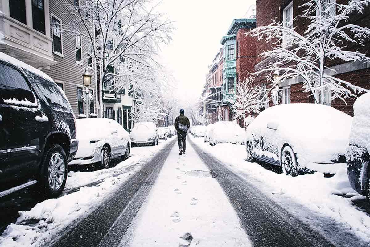 Photo of man walking down snowy street, cars snowed in on both sides of road in city