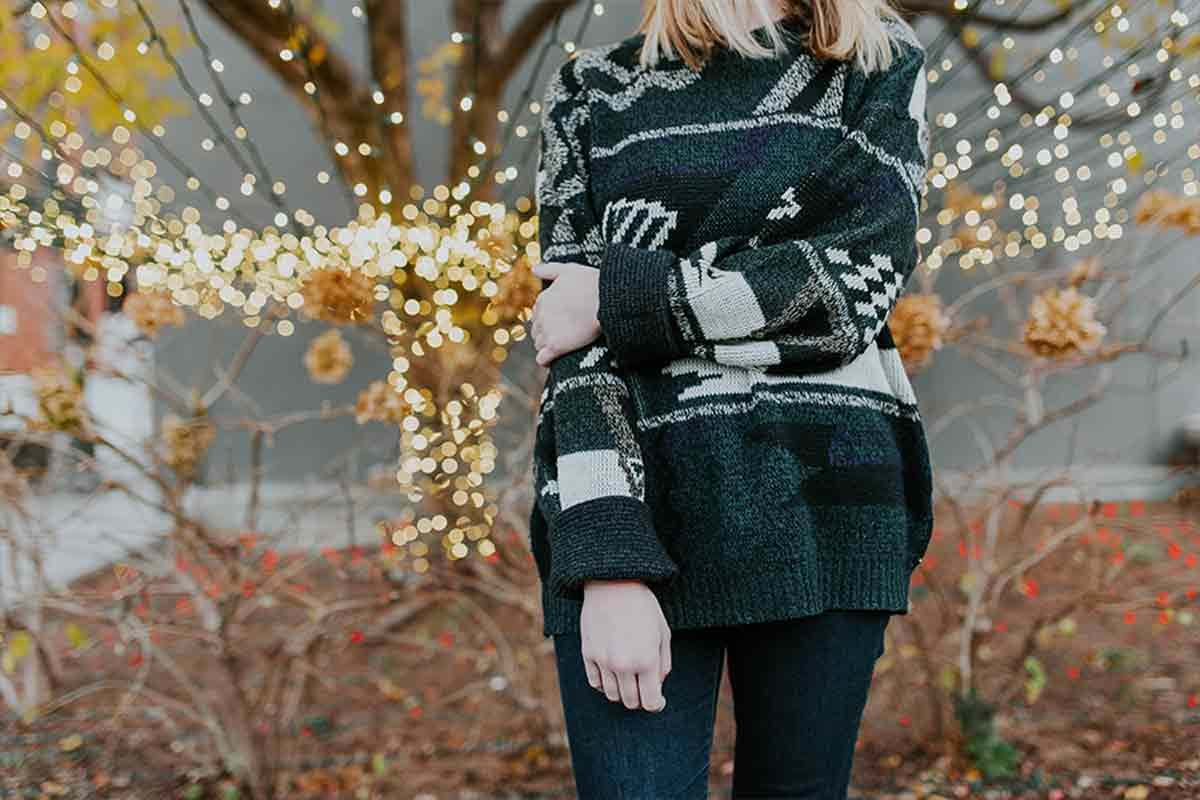 Photo of woman in sweater in front of tree with holiday lights on it.