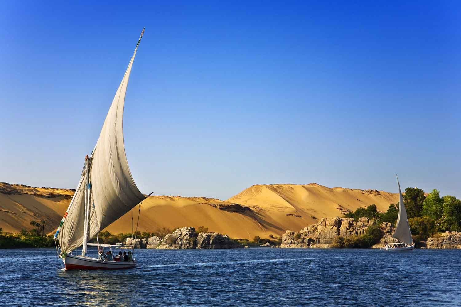 Photo of people in sailboats near Egyptian shoreline