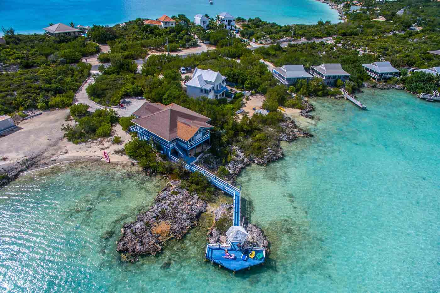 Aerial view of a blue beach house on the water
